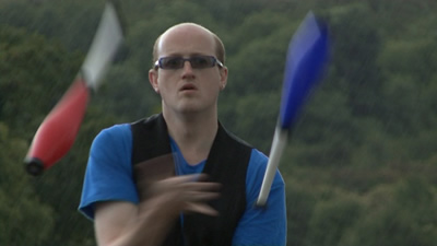 A still from my Video Showreel showing me club juggling on a very wet day on the Auld Brig in Stirling